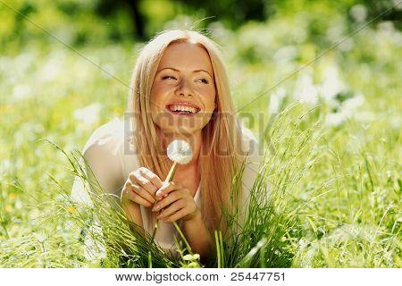 Mädchen mit einem Löwenzahn in seiner Hand liegen auf dem Rasen
