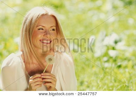 girl with a dandelion in his hand lying on the grass