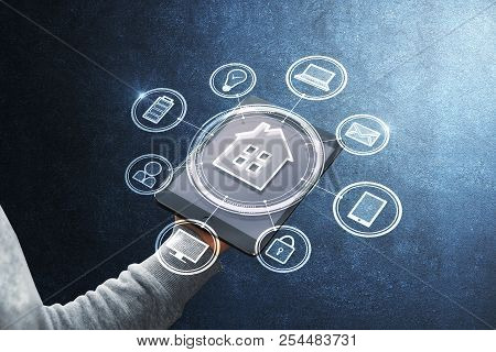 Hand Holding Touchpad With Abstract Smart Home Interface On Concrete Wall Background. Technology And