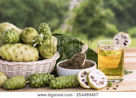 Noni Fruit Juice Or Morinda Citrifolia With Noni Slice And Noni Powder For Health On The Wooden Back