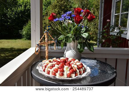 Porch With Swedish Summer Decorations Of Strawberry Cake, Flowers And A Small May Pole