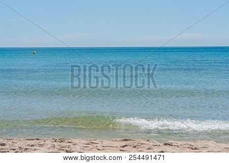 Clear Blue Water At A Sandy Beach In The Mediterranean Sea In Spain. Small Wave At The Sea On A Summ