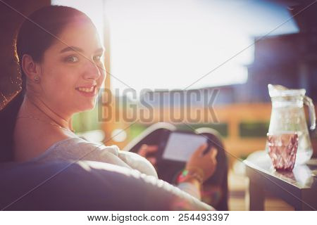 Smiling young woman sitting on sofa with touchpad