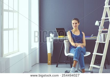 Young woman sitting at the desk with instruments, plan and laptop.