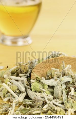 Ladle With Mountain Tea Leaves And Cup Of Tea In The Background