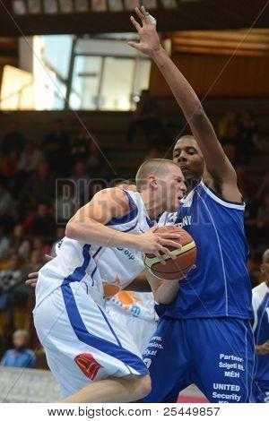 KAPOSVAR, HUNGARY - OCTOBER 15: Nik Raivio (in white) in action at a Hugarian National Championship basketball game Kaposvar (white) vs. Jaszbereny (blue) on October 15, 2011 in Kaposvar, Hungary.