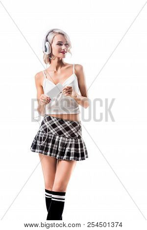 Portrait Of Beautiful Seductive Schoolgirl With Smartphone Listening Music In Headphones Isolated On