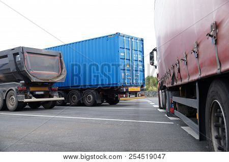 Three Different Type And Color Trucks In The Parking Lot. Tripper, Container Truck And Truck With Ta