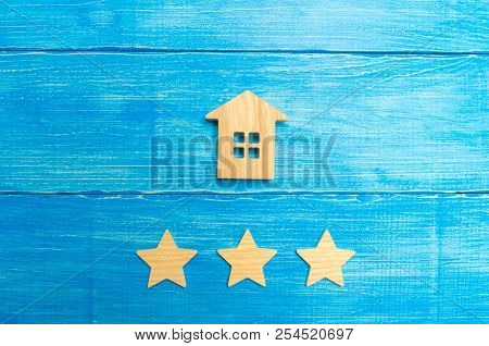 Wooden House And Three Stars On A Blue Background. Rating Of Houses And Private Property. Buying And