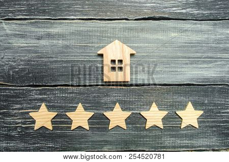 Wooden House And Five Stars On A Gray Background. Rating Of Houses And Private Property. Buying And
