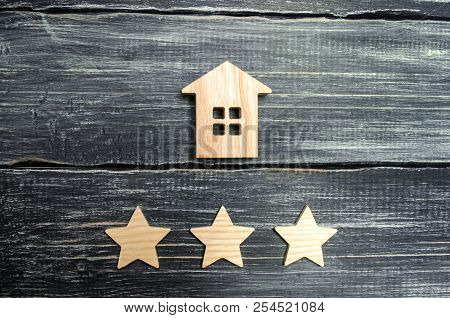 Wooden House And Three Stars On A Gray Background. Rating Of Houses And Private Property. Buying And