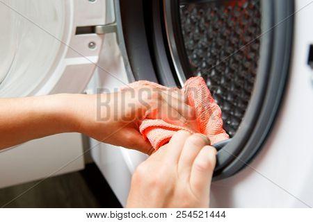Photo of woman hands wiping washing machine with open door