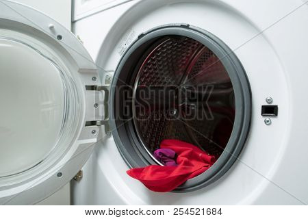 Image of open washing machine with red cloth