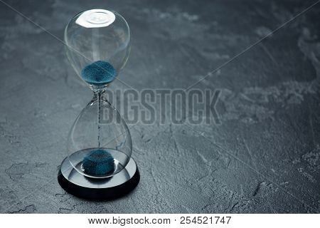 Image of hourglass with blue sand on black background