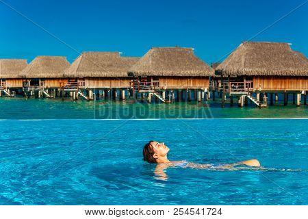 Young woman enjoying tropical beach holidays at Moorea and Tahiti, French Polynesia