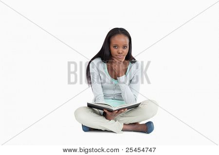 Young woman sitting on the floor thinking about her book against a white background