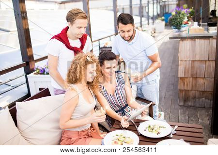 Group of young modern people sitting by served table, having lunch and watching something in touchpad