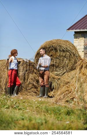Young contemporary farmers with worktools standing by hay stack and discussing work