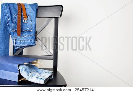 Jeans Blue Denim Fabric Clothing Textiles And A Brown Leather Belt, A Bag Stacked On A Dark Wooden C