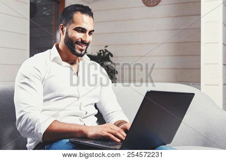 Handsome Young Businessman, Bearded Man Wears White Shirt Sitting On The Sofa And Working With Lapto