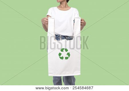 Girl Is Holding Bag Canvas Fabric With Recycle Symbol Isolated On Green Background. Eco And Save The
