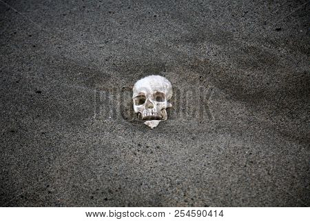 HUMAN SKULL. Human Skull washes ashore on a beach. Human Skull buried in the sand. Ocean with human skull in the sand with waves and sea foam.