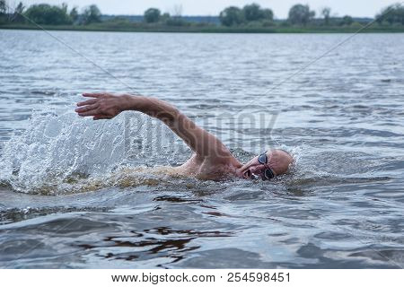An Elderly Muscular Man In Swimming Goggles Swims With A Crawl Style