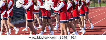 A High School Cheerleading Squd Is Cheering To The Fans In The Stands At Their Homecoming Football G