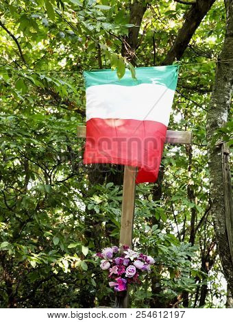 Italian Flag Over Cross With Flowers In The Woods