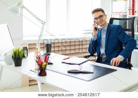 A Young Man Is Sitting At A Table In The Office And Talking On The Phone.