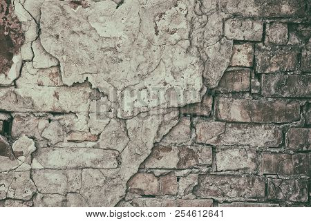 Old Brick Wall With Cracked Fallen Off Cement Plaster. Crumbled Aged Rough Brickwork Texture. Retro