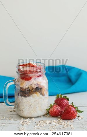 Overnight Oats With Fresh Strawberry Served In A Tall Glass Jar On Wooden Table With Blue Napkin