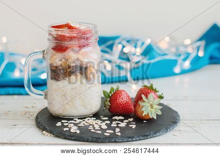 Overnight Oats With Strawberry Served In A Jar On Black Slate Board With Fresh Whole Berries, Blue N