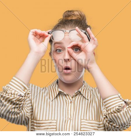Young blonde business woman doing ok gesture shocked with surprised face, eye looking through fingers. Unbelieving expression.