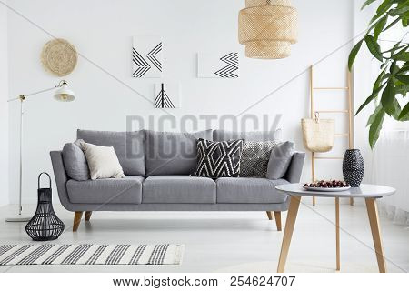 Real Photo Of A Scandi Living Room Interior With Cushions On Gray Couch, Cherries On Wooden Table An