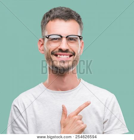 Young tattooed adult man cheerful with a smile of face pointing with hand and finger up to the side with happy and natural expression on face looking at the camera.