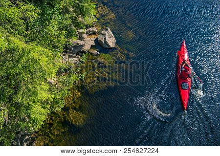 River Kayaker Aerial View. Caucasian Sportsman In The Red Kayak Paddling On The Scenic River Along T