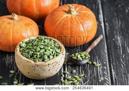 Bowl With Pumpkin Seeds And Small Pumpkin On A Rustic Table. Selective Focus