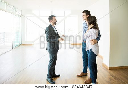 Male Broker Discussing With Couple While Standing In New House