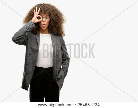 African american business woman wearing glasses doing ok gesture shocked with surprised face, eye looking through fingers. Unbelieving expression.