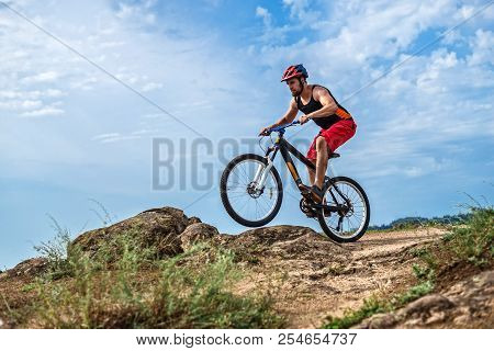 Concept Of Extreme Cycling, A Biker On A Mountain Bike On The Blue Sky Background, Free Space.