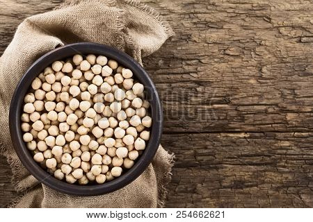 Raw Chickpeas Or Garbanzo Beans (lat. Cicer Arietinum) In Rustic Bowl, Photographed Overhead On Rust