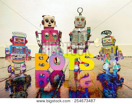 four retro robot toys and the word BOTS on a wooden floor