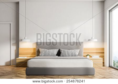 Interior Of A Modern Bedroom With White Walls, A Wooden Floor, A Double Bed And Two Bedside Tables W