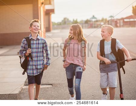 Candid Photo of a group of smiling elementary school students in the playground after school. Back to school concept photo. Real kids walking home from school and having fun