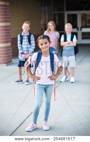 Photo of a diverse group of smiling elementary school students standing in front of the school building. Selective focus on the cute girl in front. Standing out from the crowd