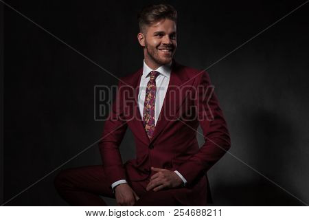portrait of smiling elegant man in grena suit looking to side while sitting on wooden chair on grey background