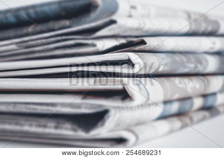 Newspapers Folded And Stacked On The Table. Selective Focus.