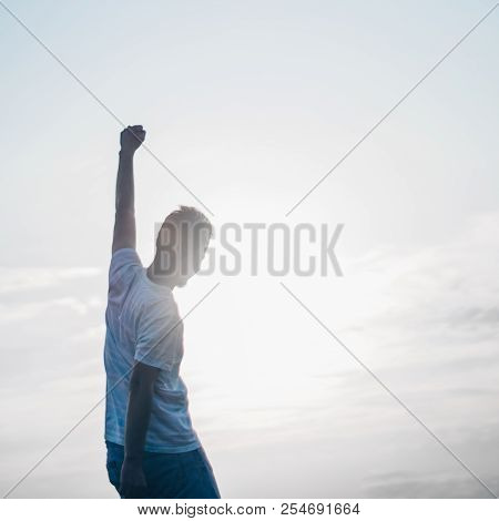 Jumping Man. Young Crazy Man Is Jumping On Rocky Summit Above Landscape. Silhouette Of Jumping Man A