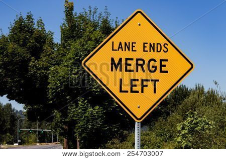 Lane Ends Merge Left Sign With Trees And A Blue Sky